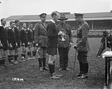 A black and white photo of a rugby field in which three men in military uniform, one of whom is King George, present a silver trophy to a rugby player dressed in black kit. Behind in a line are the rest of the team.