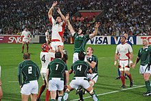 Two rows of opposing players, green to the fore, white behind, each aid a jumping player from their team by lifting him towards an off-picture ball travelling overhead